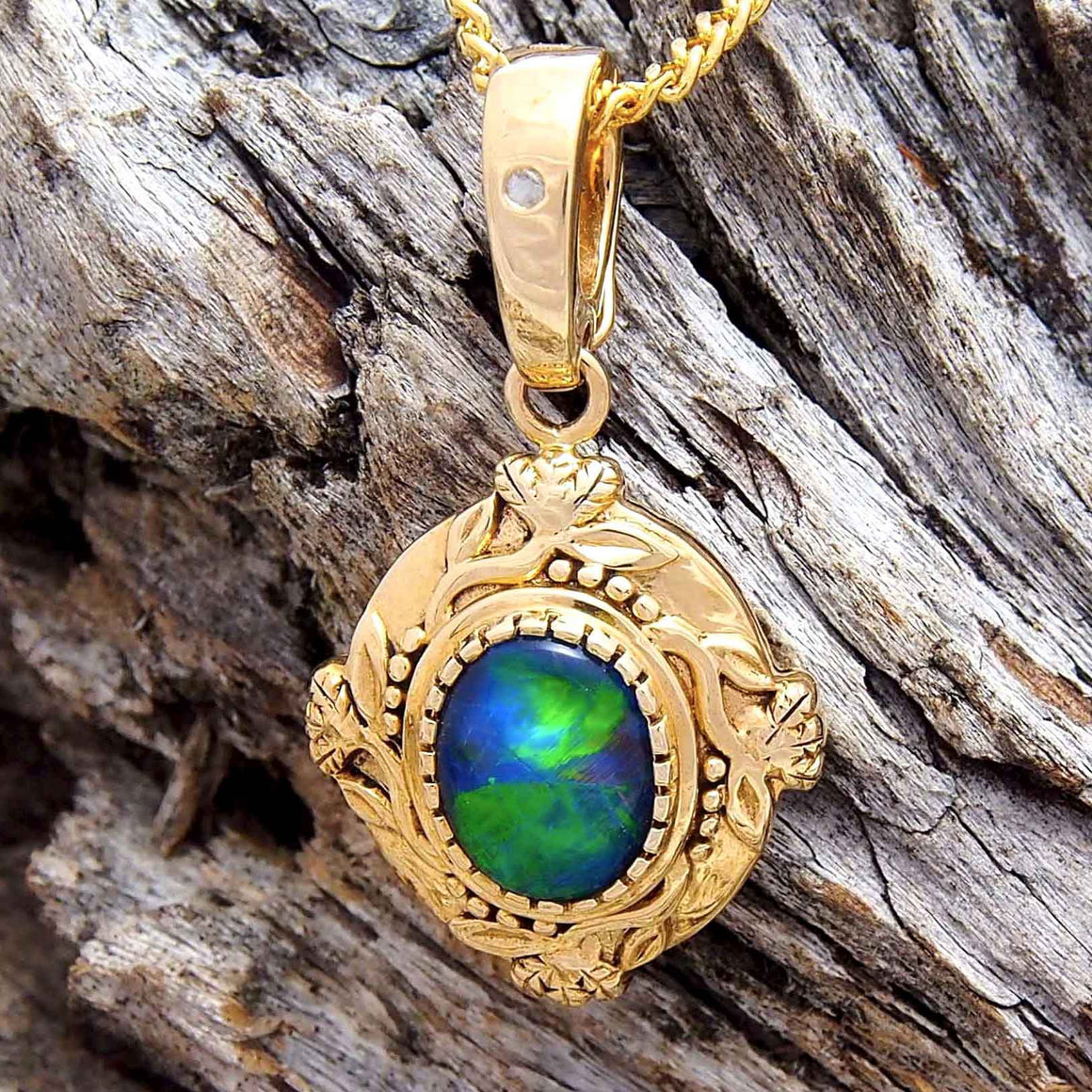 Intricate 9ct yellow gold floral design necklace pendant with pearl enhancer clasp, bezel set with a rich blue and green oval triplet opal and featuring a flush set white diamond