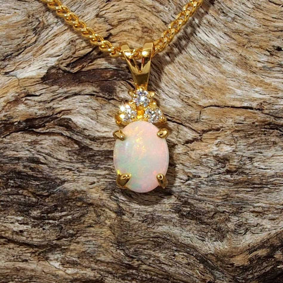 Elegant gold plated silver necklace pendant claw set with a colourful oval shape white opal with three cubic zirconias.