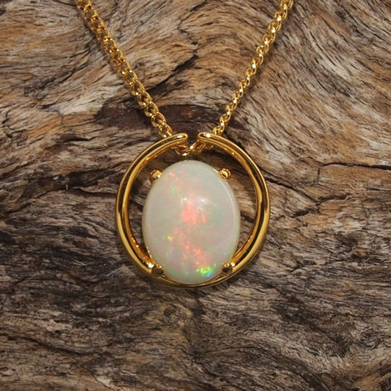 Modern gold plated silver open circle design slide necklace pendant claw set with a solid white opal with green and red flashes.