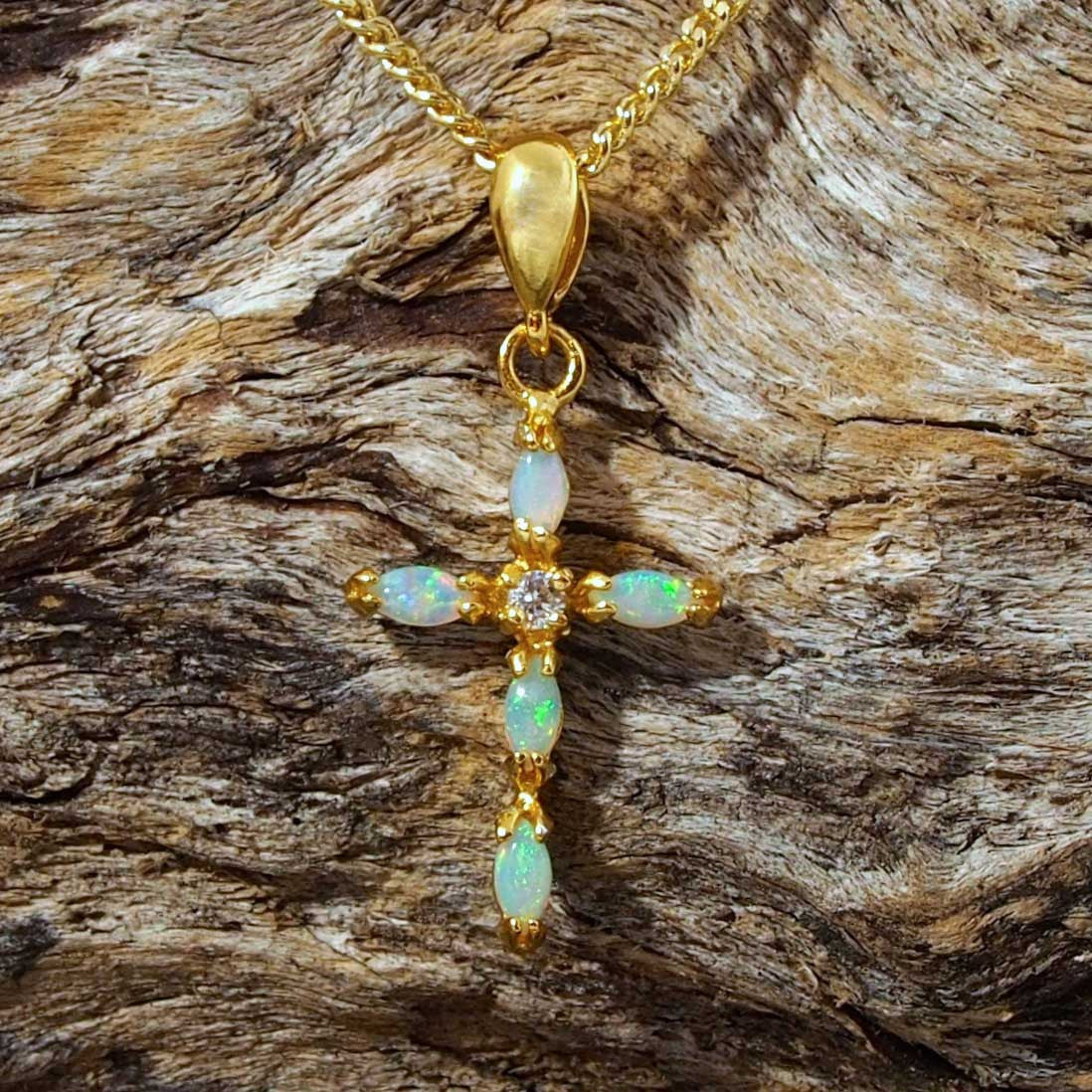 Opal cross necklace pendant claw set with 5 crystal opals and a cubic zirconia.