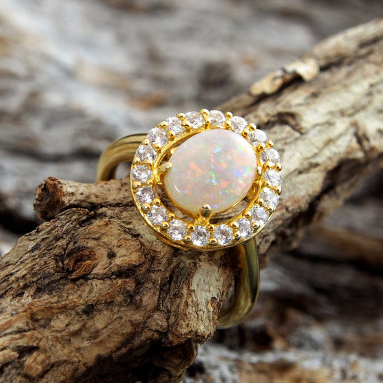 Elegant gold plated sterling silver dress ring claw set with a beautiful South Australian oval solid crystal opal surrounded by eighteen cubic zirconia.