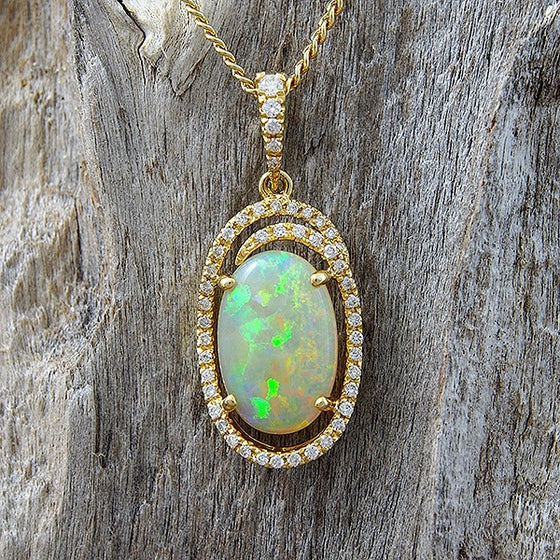 Stunning 18ct yellow gold necklace pendant set with a multi-colour South Australian solid crystal opal and encircled with .28ct white diamonds.