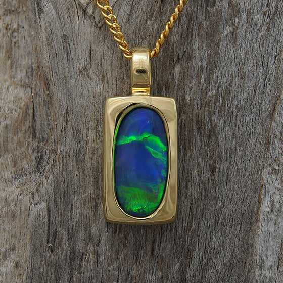 Elegant 18ct yellow gold necklace pendant bezel-set with a vibrant blue, green Lightning Ridge solid black opal