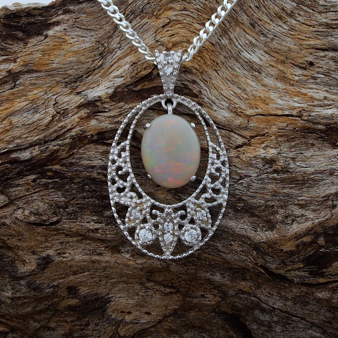 Sterling silver lace design necklace pendant claw set with a colourful oval white opal and eight cubic zirconias.