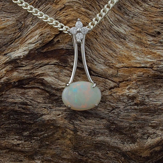 Elegant necklace pendant claw set with a colourful oval shape white opal and four cubic zirconias.