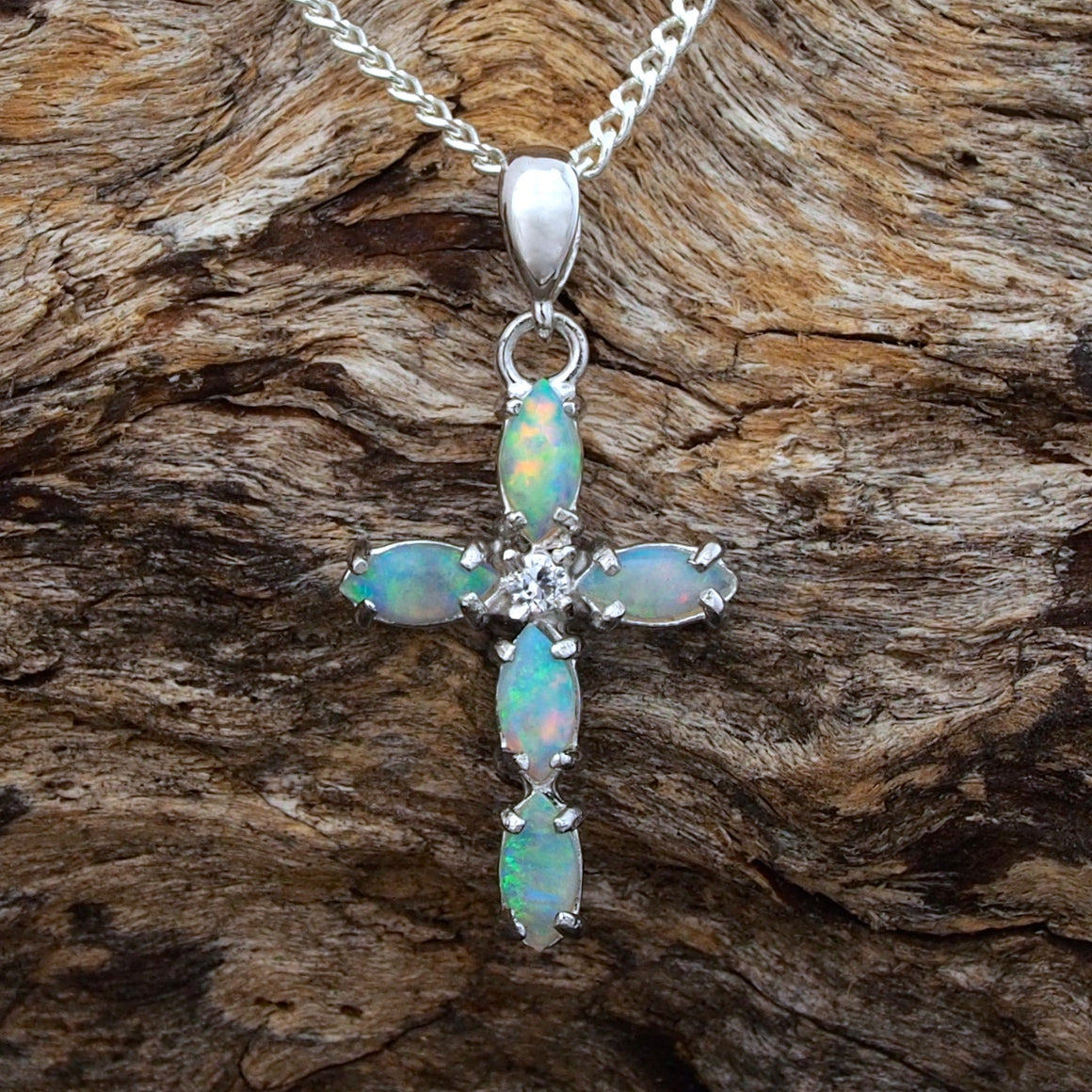 Opal cross necklace pendant claw set with five crystal opals and a cubic zirconia.