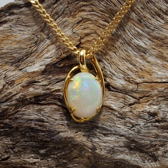 Elegant necklace pendant claw set with a colourful oval shape white opal.