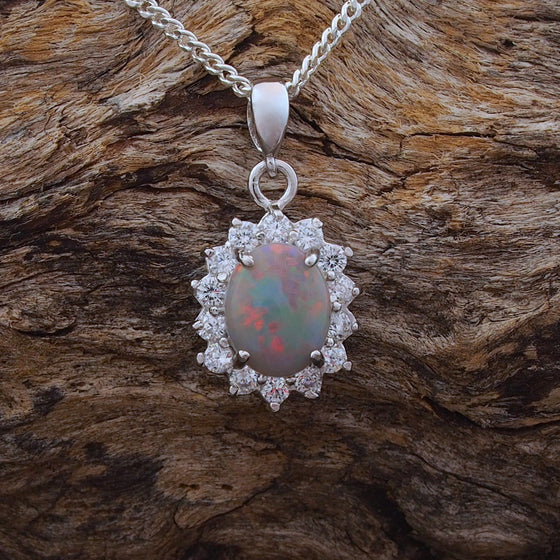 Beautiful sterling silver princess design necklace pendant claw set with a colourful oval white opal and fourteen cubic zirconias.