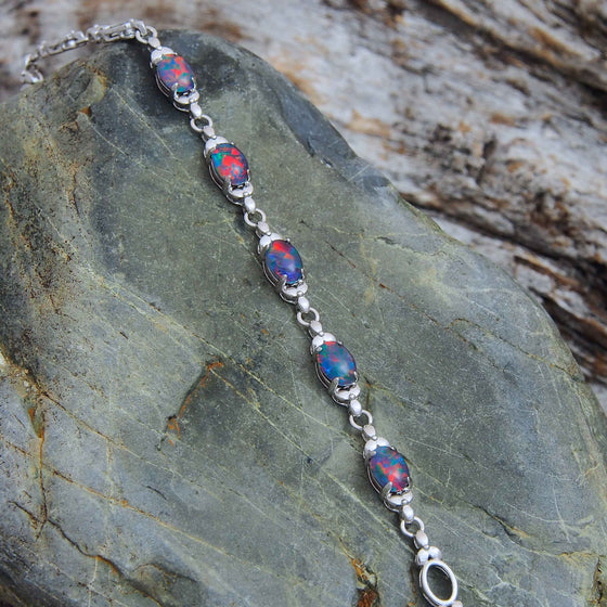 Sterling silver flower design bracelet claw-set with five beautiful multi-colour oval triplet opals