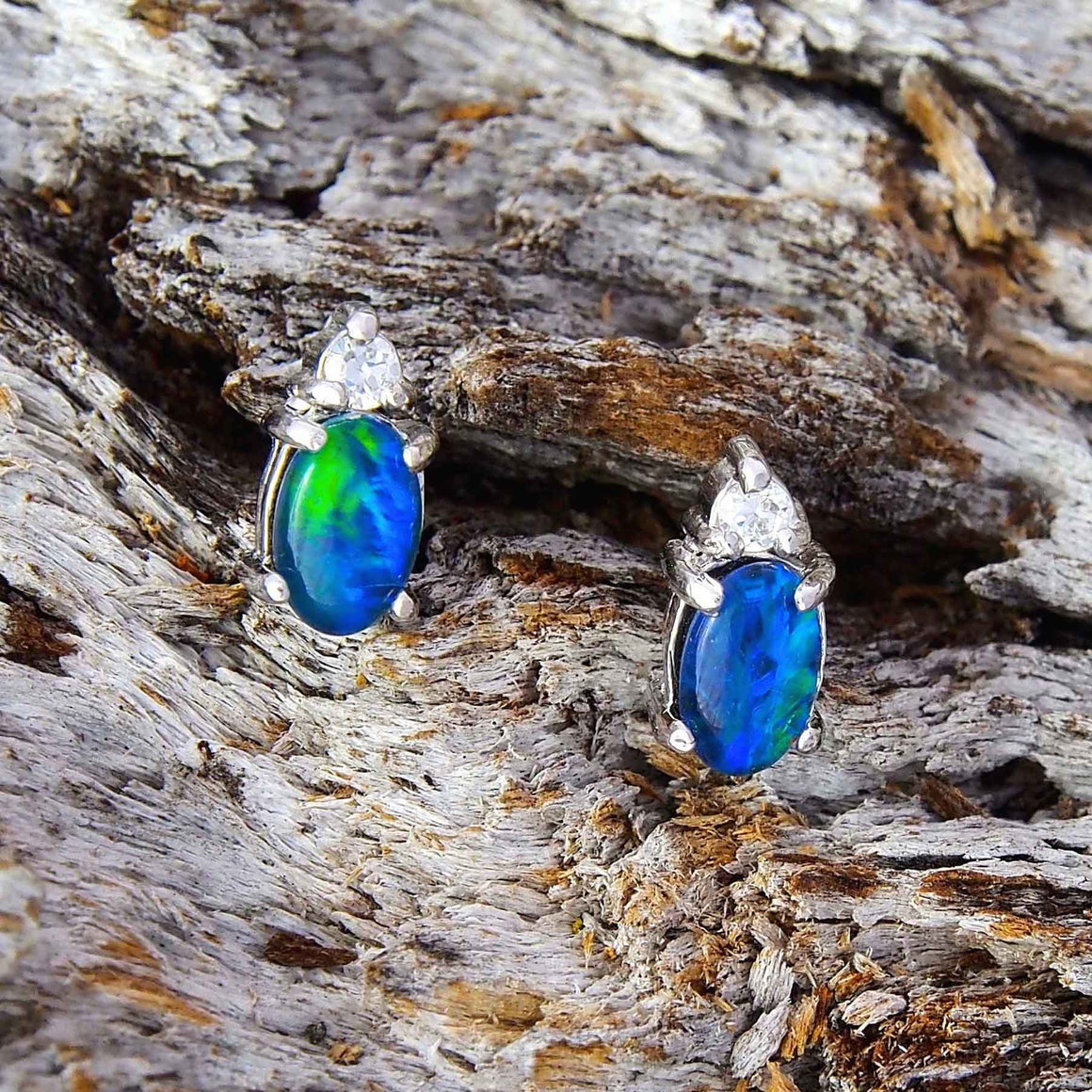 Stylish sterling silver oval stud earrings each claw set with a vibrant blue and green triplet opal and a diamante