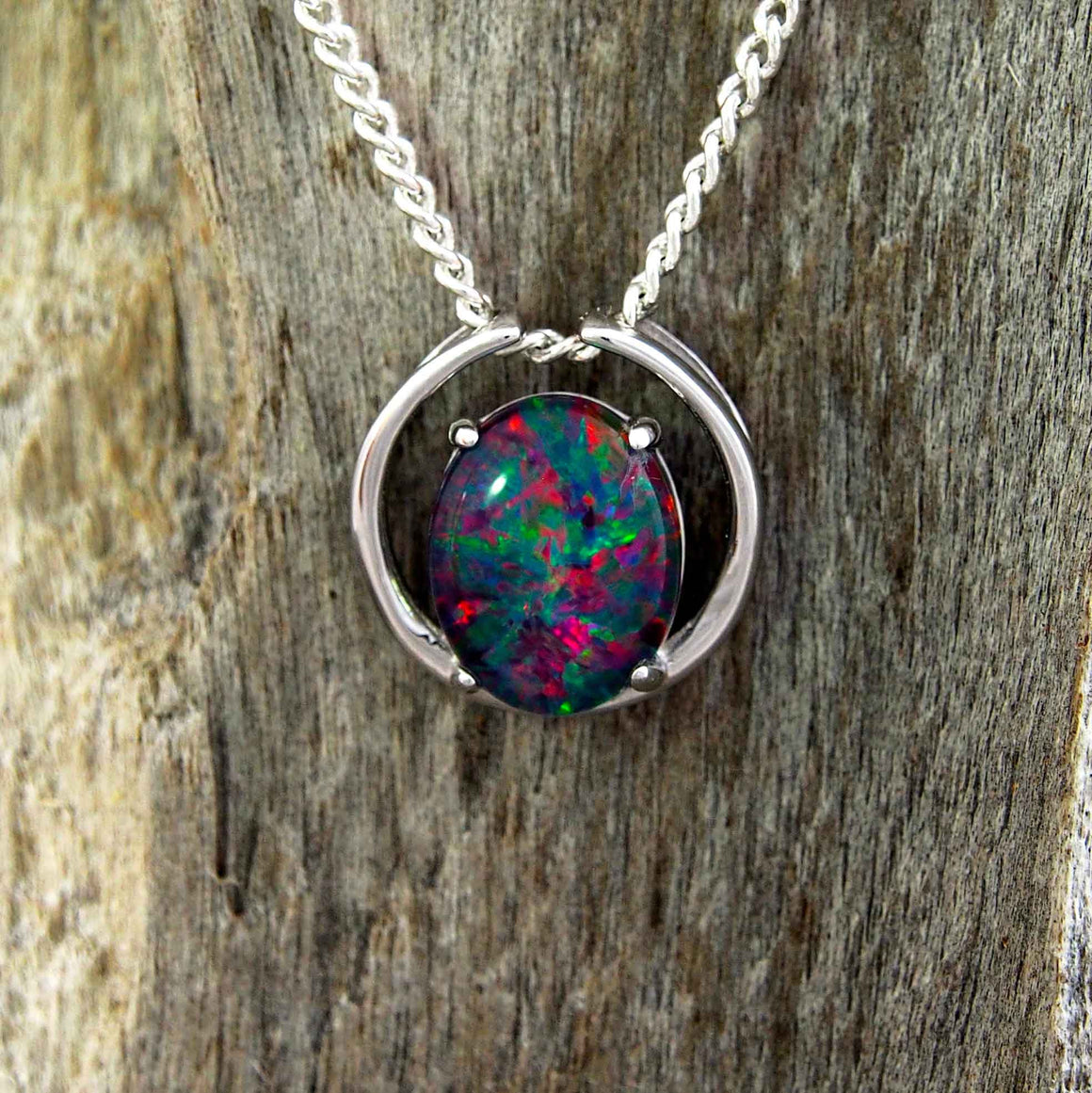 Modern sterling silver open circle design slide necklace pendant claw set with a colourful oval triplet opal.