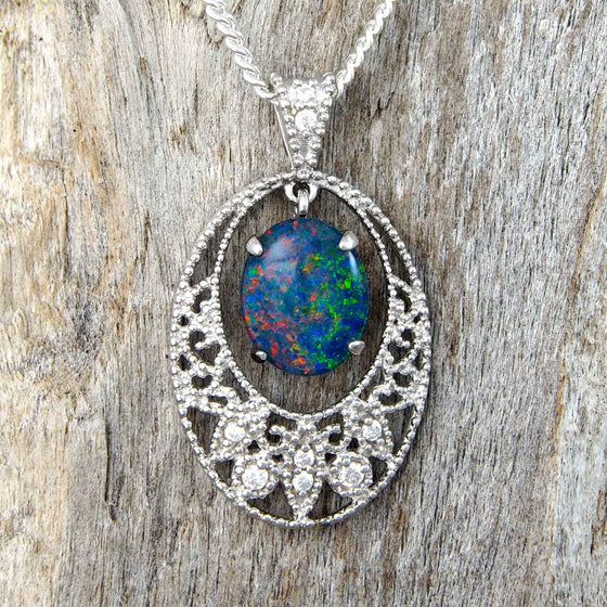 Sterling silver lace design necklace pendant claw set with a colourful oval pinfire patterned triplet opal and eight cubic zirconias.