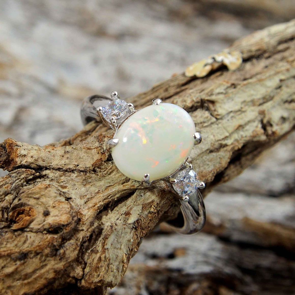 Elegant sterling silver ring claw set with a beautiful multi-colour oval South Australian solid white opal with two shoulder set cubic zirconia.