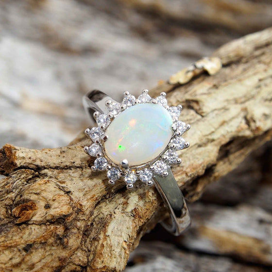 Pretty sterling silver princess design ring claw set with a beautiful green South Australian oval solid crystal opal and 16 cubic zirconias.