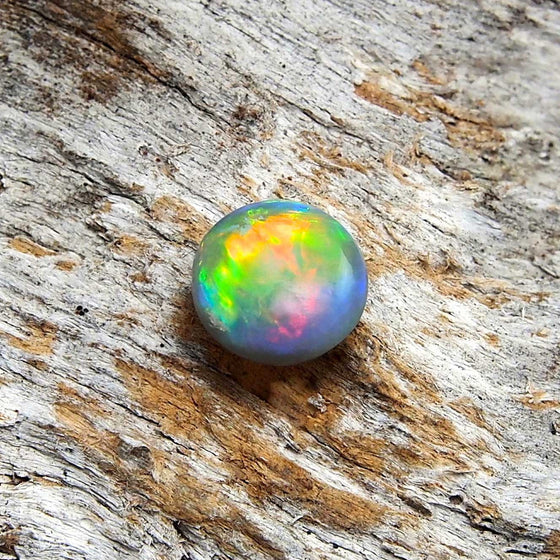 Beautiful round rolling flash patterned solid Lightning Ridge semi-black opal with orange and green body colour and pink and blue highlights, ideal for a ring or necklace pendant setting