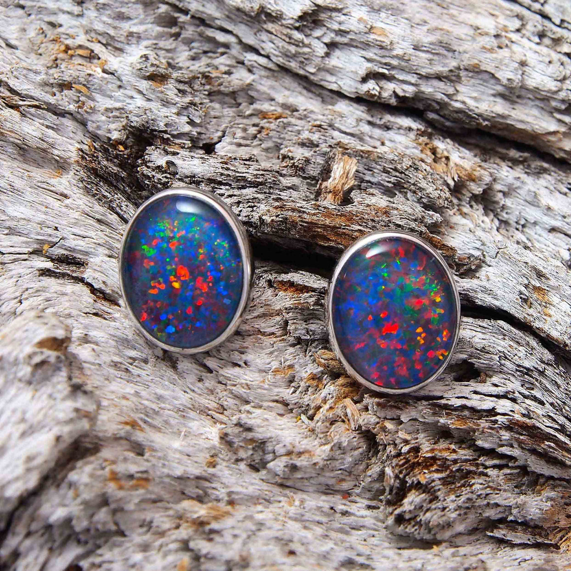 Elegant 9ct white gold oval stud earrings bezel set with multi-colour floral patterned triplet opals