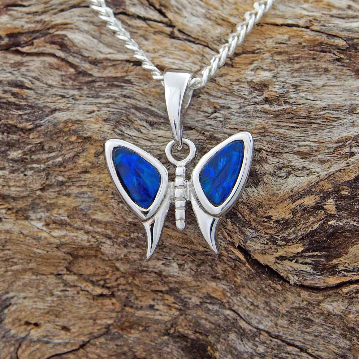 Sterling silver butterfly necklace pendant bezel set with two bright, blue coloured triangle-shaped doublet opals.