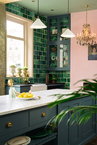 Janery Blush pink walls paired with navy cabinets and emerald green tile