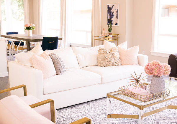 Janery White sofa with blush and gray accessories and gold toned hardware and furniture