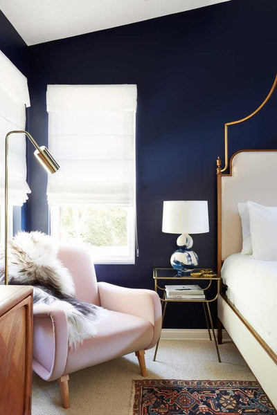 Janery Decorating with Blush Tones Navy blue walls with blush pink armchair in master bedroom