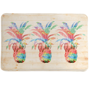 Colorful Pineapples Memory Foam Rug features pineapples set on a textured background designed to look like a wooden board and features splashes of paint.