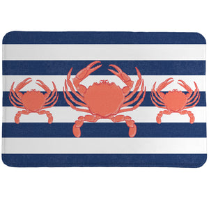 Crab Stripe Memory Foam Rug showcases a classic navy blue nautical stripes that serves as the background to three coral-colored crabs.