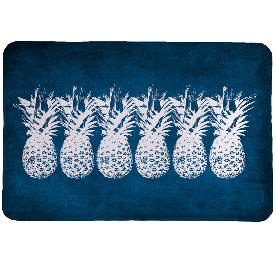 Indigo Pineapples Memory Foam Rug features a row of white pineapples standing out against a deep indigo blue background