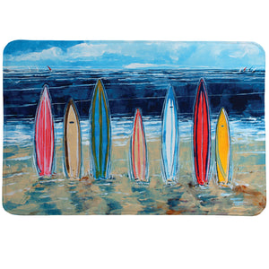 Surfboards Memory Foam Rug shows surfboards resting in the sad against an ocean backdrop.