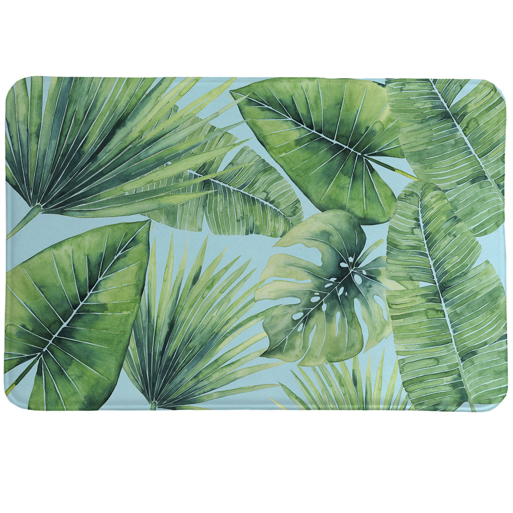 Tropical Palm Tree Leaves Memory Foam Rug features palms, fronds and banana leaves in a watercolor technique set before a blue backdrop.