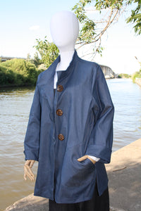 Blue organic denim jacket. Loose fit. Cuffed sleeve. 3 button closure.  2 large pockets. Hip length.