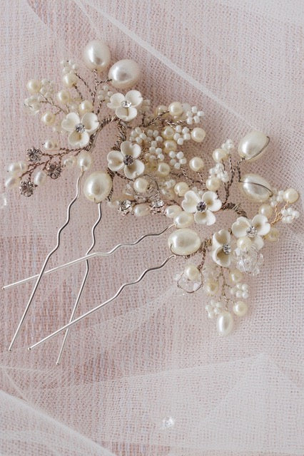 Floral hair pins lying against white tull