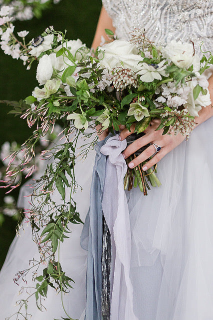 A bride wearing a light blue wedding gown holding a dramatic bouquet and wearing a sapphire wedding ring.
