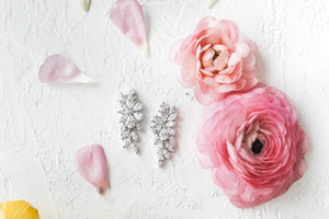 The Peony earrings with pink roses and scattered petals lying against a white background