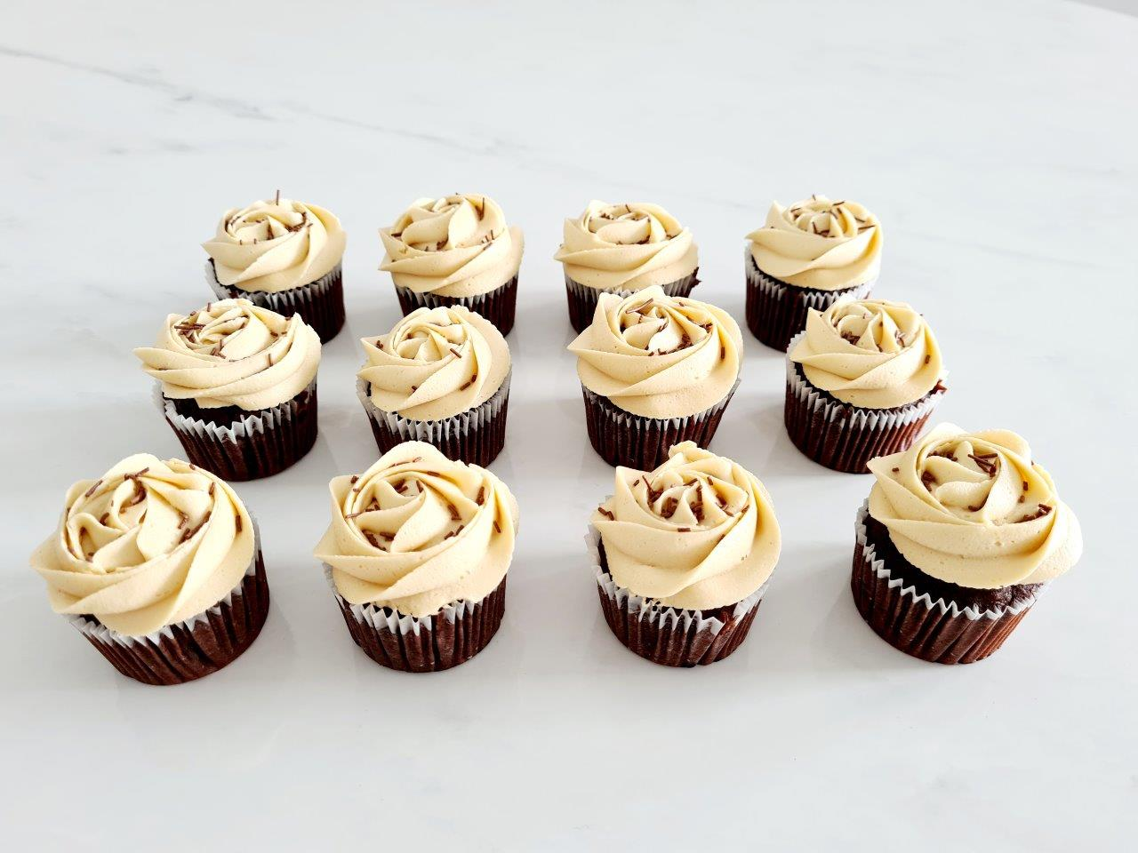 Coffee buttercream topped with chocolate sprinkles on vanilla or chocolate cupcakes