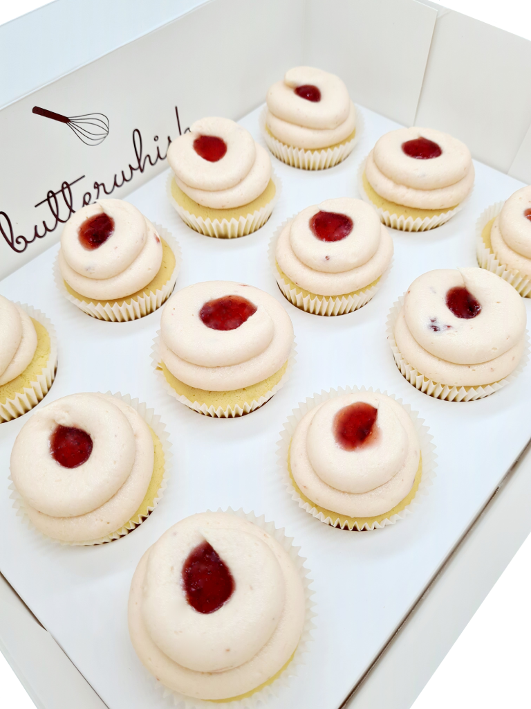 Strawberry buttercream topped with strawberry jam on vanilla cupcakes