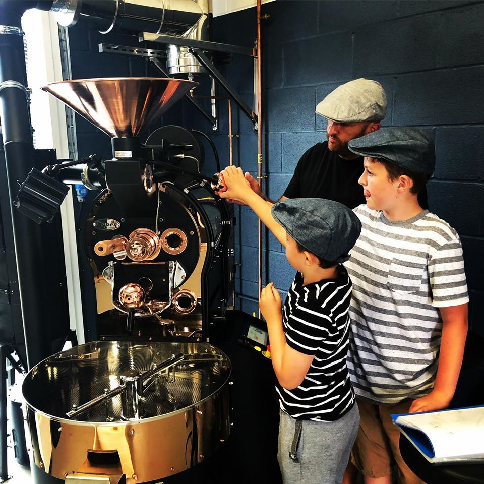 Image shows Dad teaching two young sons how to roast specialty coffee on black and copper coloured toper coffee roaster machine. Boys and Dad are wearing flat caps at the Flat Cap Coffee Roasting Company's Roastery in Wiltshire, UK