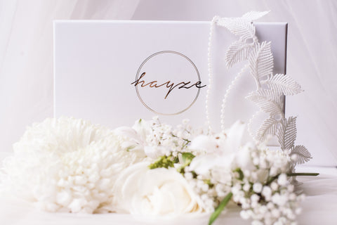 Image of a white wedding garter. It had a feather style trim and 3 pearl chains that drape from the garter and an adjustable clasp. It's displayed on a Hayze Bridal Gift Box