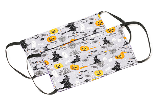 Handmade Halloween cloth face masks with witches and pumpkins on gray fabric