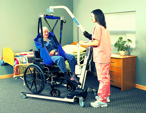 Patient lift and sling are being used by an elderly and a caregiver nurse in homecare setting