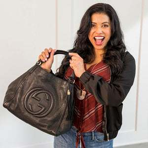 Happy smiling woman wearing a black jacket holding a black Gucci handbag.