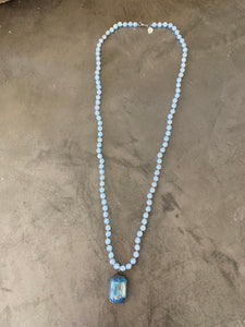 long beaded necklace with faceted glass pendant