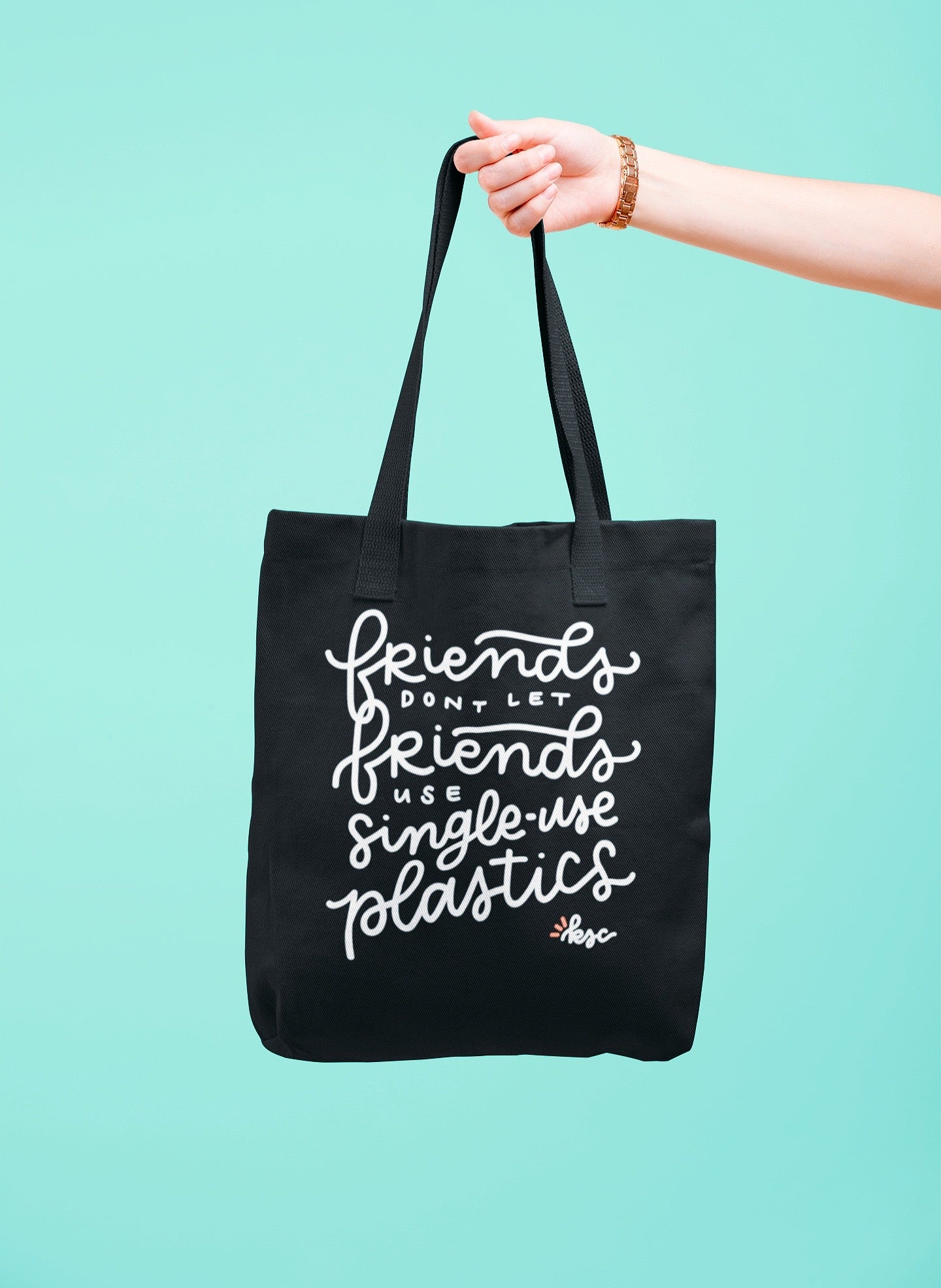 Hand holding a black Eco Tote with the eco-friends design on it in front of a teal background | Kerra Sun Creative