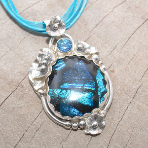 Dichroic glass pendant in shades of blue in a setting of sterling silver. (N378)