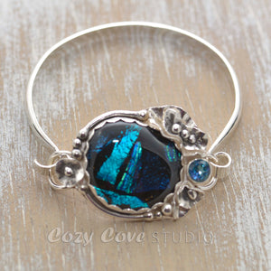 Statement cuff bracelet with a dichroic glass in shades of blue in a setting of sterling silver. (B378)