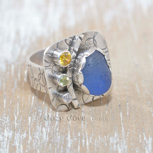 Sea glass statement ring with cornflower blue sea glass accented with sparkly CZs in sterling silver. (R388)