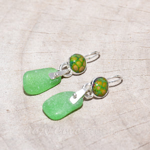 Sea glass and enamel earrings accented with sapphire cabochons in sterling silver settings.