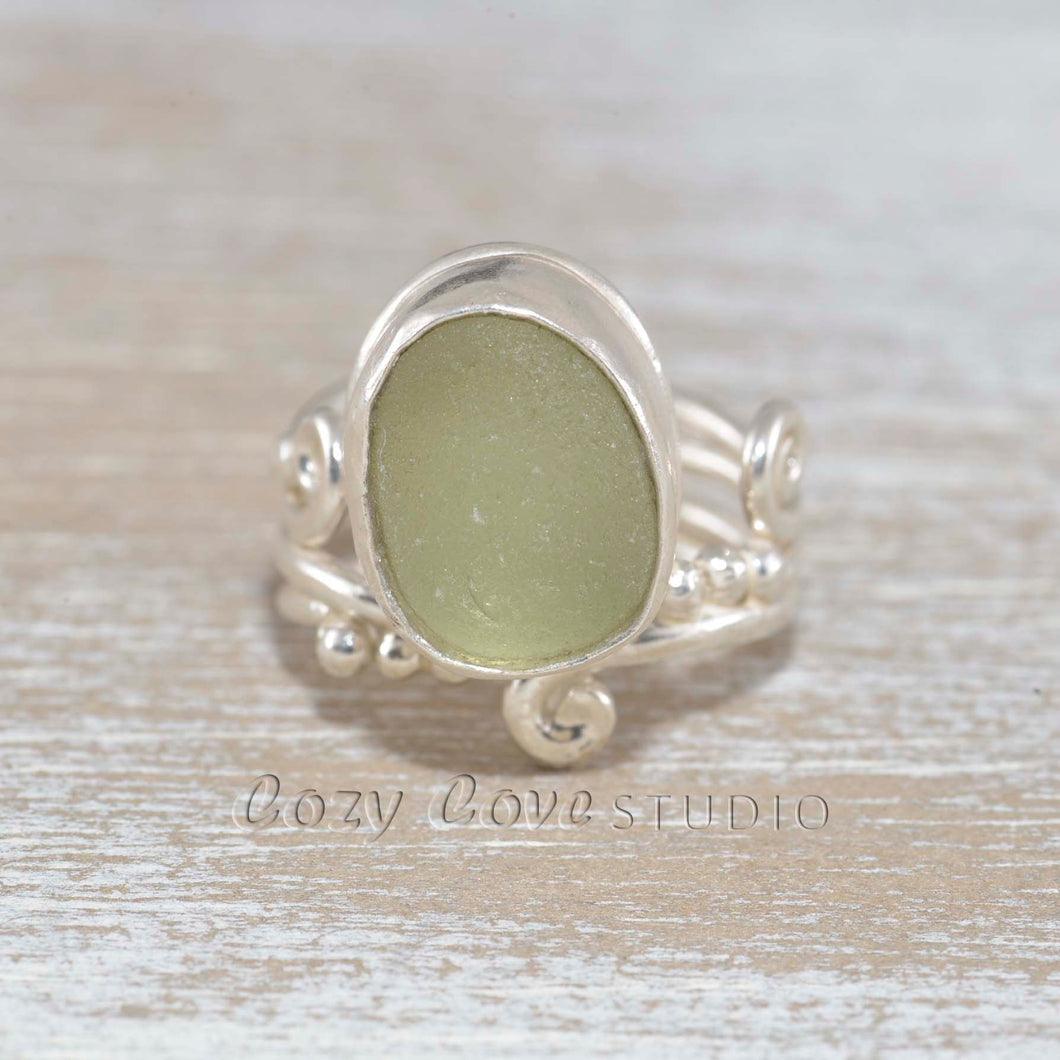 Adjustable sea glass ring with pale lime green sea glass  in a handcrafted setting of sterling silver (R476)