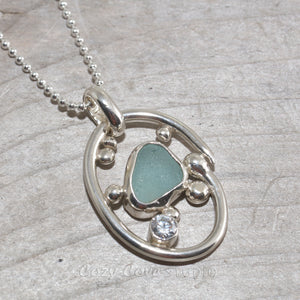 Sea glass necklace in a hand crafted tarnish resistant sterling silver setting accented with pebbles and a sparkly CZ on an adjustable leather cord. (N492)