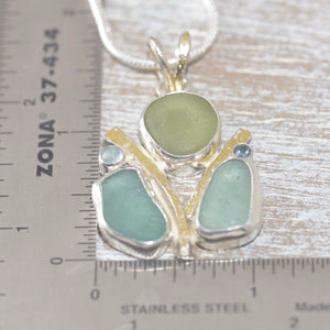Sea glass pendant necklace with tones of green and blue sea glass in a hand crafted setting of tarnish resisant sterling silver accented with 22 K gold (N506)