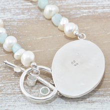 Load image into Gallery viewer, Sea glass pendant in a handcrafted sterling silver setting accented with a pale topaz and a milky aquamarine on a hand knotted necklace of cultured pearls and amazonite chips. (N517)